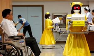 Robots dressed in nurse outfits carrying medical documents work next to Thai patients at Mongkutwattana General Hospital in Bangkok.