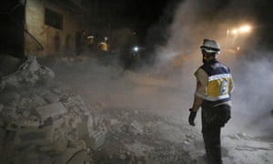 Members of the Syrian White Helmets amid the rubble of a building following a reported government air strike in Maaret al-Numan in Idlib