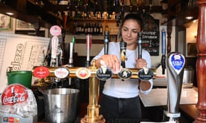 A pub employee prepares for reopening in Soho, London.