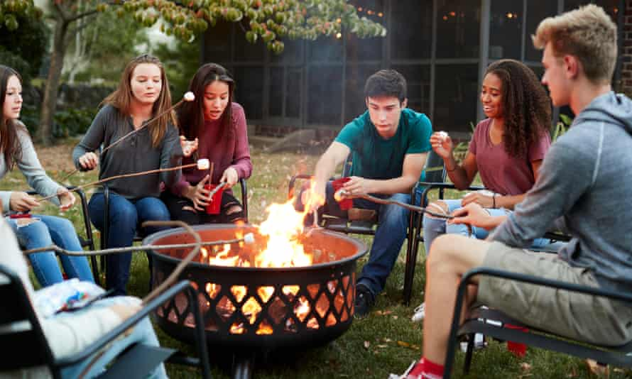 Friends sit round a fire pit toasting marshmallows