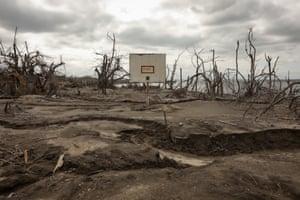 A basketball ring submerged among volcanic ash deposits