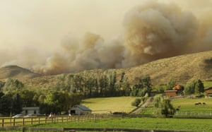 Flames and smoke rise on a hillside above homes on Twisp River Road