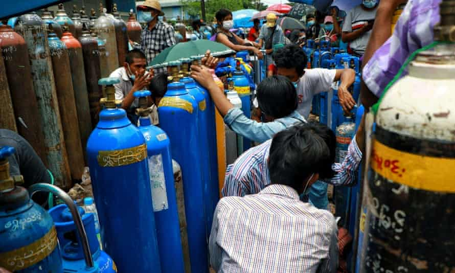 People wait in line next to oxygen tanks to be refilled outside the Naing oxygen factory at the South Dagon industrial zone in Yangon, Myanmar.