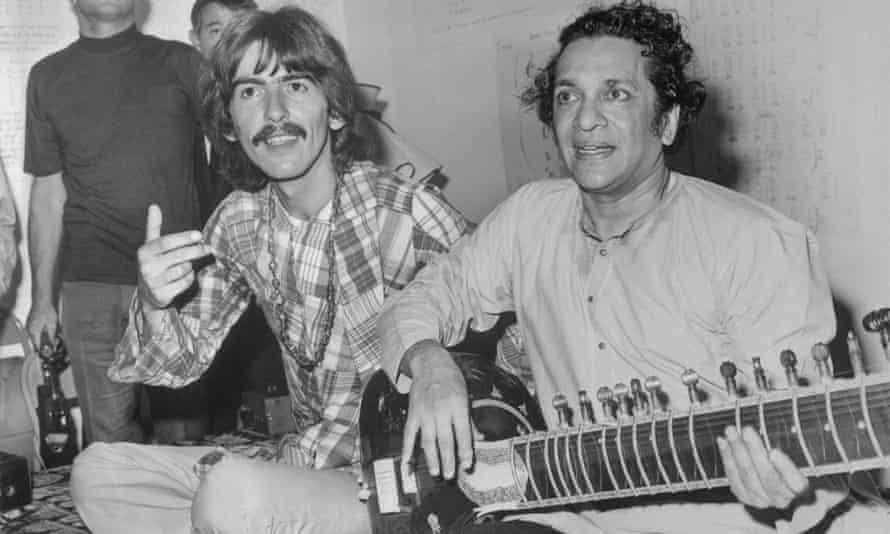 George Harrison listens as Ravi Shanker plays the sitar in 1967.