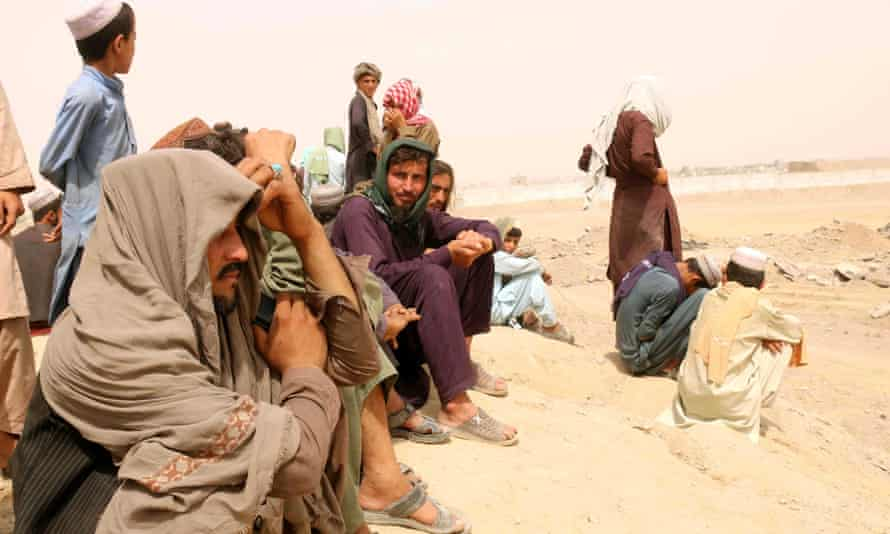 People stranded at the Pakistani-Afghan border wait by the road
