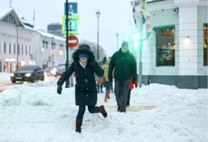 People pick their way through the snow while crossing a street.
