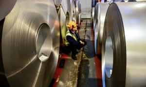 A worker inspecting rolls of steel