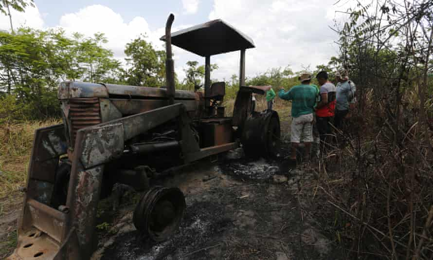 Ka'apor Indians stand next to a logging tractor that they discovered and set on fire inside the indigenous territory one month before.