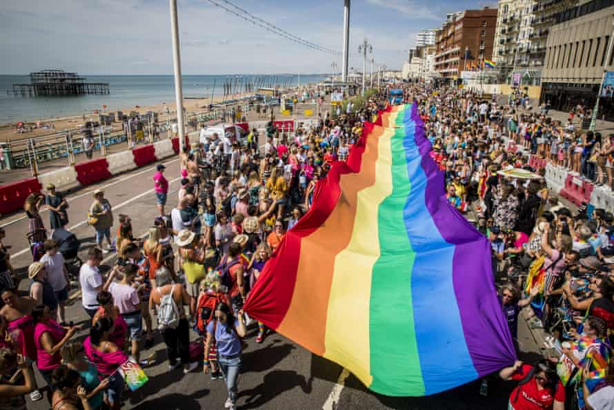 A giant rainbow Pride flag is carried along the sea front during Brighton Pride 2018.
