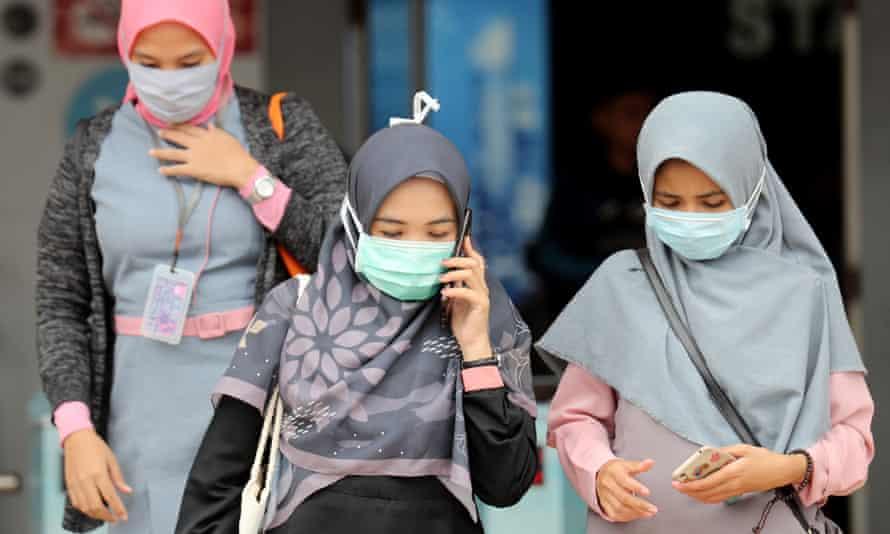 Indonesian women wear masks in a public area in Depok, West Java, Indonesia