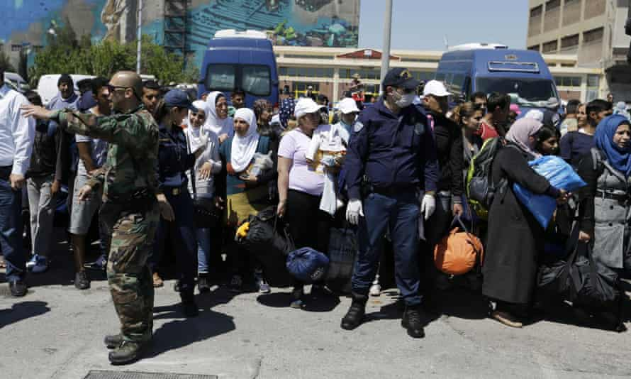 Athens coastguards give directions to refugees being transported out of the port of Piraeus.