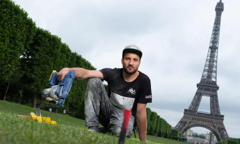 Saype at the Champs de Mars, Paris, working on his Beyond Walls land art project.