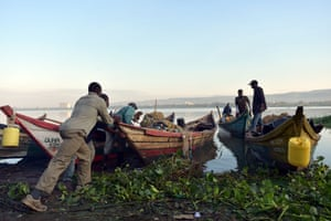 Fishermen push out a boat at dawn on Lake Victoria