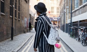 Side view of woman in hat and striped coat walking in street
