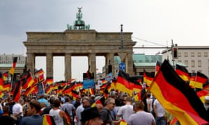 People wave German flags during an AfD rally at the Brandenburg Gate in Berlin.