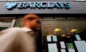 Pedestrian walks past a Barclays branch