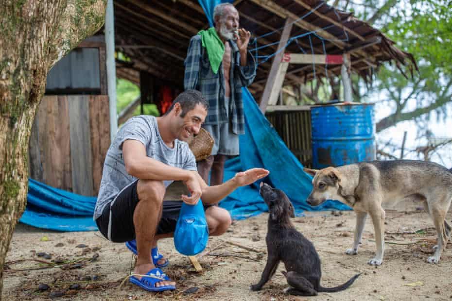 Ari Sirwan, 26 years old, greets local dogs.