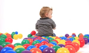 Small boy sitting between coloured balls