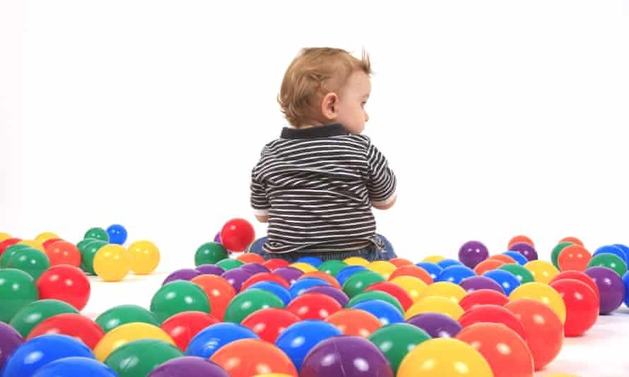 Small boy sitting between coloured balls