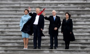 Donald Trump's long red tie narrowly misses Mike Pence as he, Melania Trump, the vice-president and Karen Pence wave at the US Capitol during Trump's inauguration on 20 January 2017