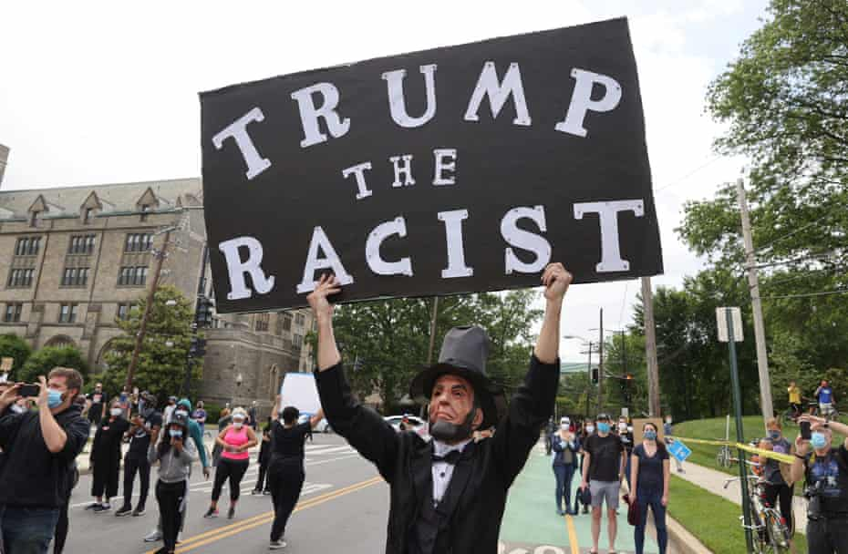 A man dressed as Abraham Lincoln holds up a sign as Donald Trump's motorcade passes in Washington in June.