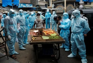 Mumbai, India,  a vegetable vendor pushes his handcart past healthcare workers