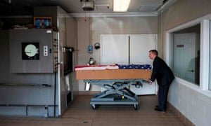 A crematory operator pushes the body of an unnamed veteran who died of Covid-19 to an incinerator in Frederick, Maryland.