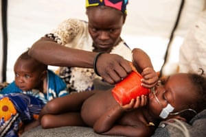Gbane Agatha gives her two-year-old daughter Marceline Mini water in Baboua district hospital. Marceline is being treated for measles with respiratory complications. Also pictured is her sister Adama Cecile