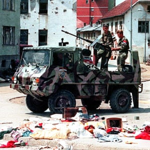 A Bosnian Serb armed vehicle crew drives through the deserted streets of Srebrenica.
