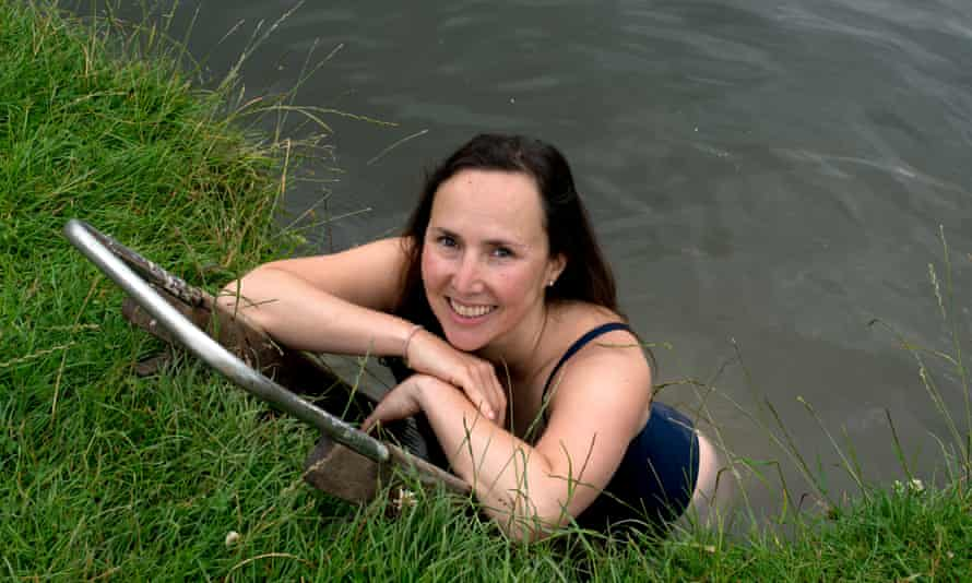 Camila Ilsley standing in the river, leaning on the riverbank and smiling at the camera above her, with a float or small bodyboard
