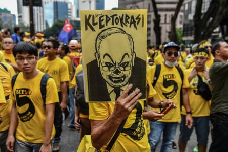 A protester holds a placard with a caricature depicting Malaysian Prime Minister Najib Razak during a mass rally calling for Razak's resignation, in Kuala Lumpur