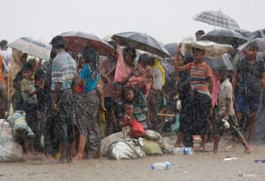 Rohingya refugees stand in heavy rain as they are held by the Bangladesh border guard after illegally crossing the border, in Teknaf