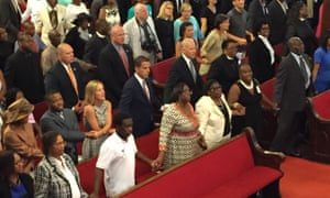 "Joe Biden, center, with his son and daughter-in-law Hunter and Kathleen Biden, to his right, sing ""We Shall Overcome"" while joining hands with Emanuel AME church members Sunday 28 June 2015."
