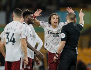 Referee Craig Pawson points to the tunnel after showing David Luiz of Arsenal a red card.