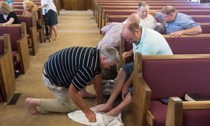man washes another man's feet in church