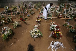 A priest arranges flowers at the site of a mass burial in Negombo.