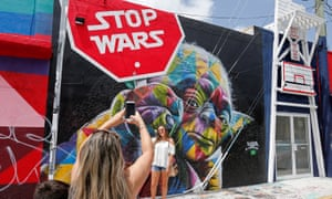 Visitors take pictures of a mural in Wynwood.
