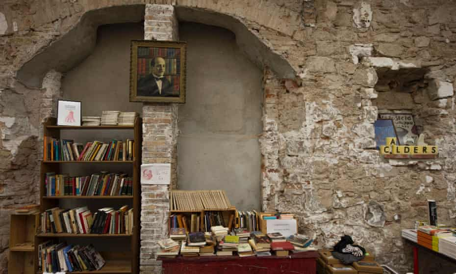 Exposed brick interior of Calders bookshop in Barcelona, with books stacked and on shelves.