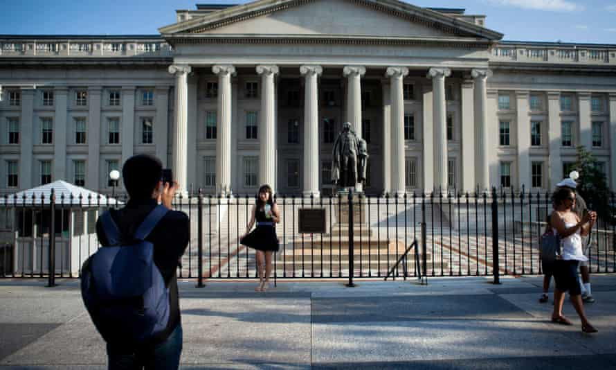 A tourist poses in front of the US treasury department in Washington DC