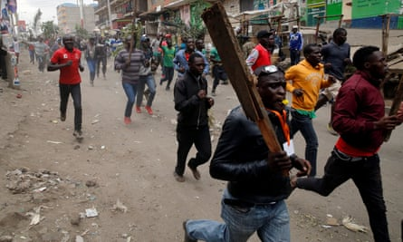 Protesters carry sticks as they run along a street in Mathare, a slum area north of Nairobi
