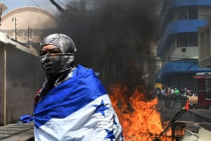 Tegucigalpa, HondurasA student of the National Autonomous University of Honduras wrapped in a Honduran national flag is seen next to a burning roadblock during a protest against the approval of education and healthcare bills.