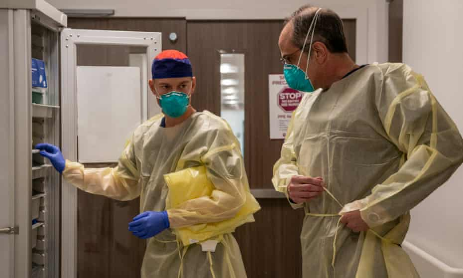 Matt Robinson and Bobby Bluford put on PPE before entering the Covid isolation unit at Methodist University hospital in Memphis.