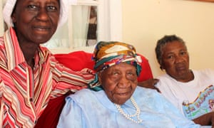 The world's oldest person Violet Brown sitting with a care giver either side of her at her home in Jamaica