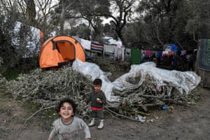 Children play by olive branches cut to make fire in the makeshift migrant camp on the island of Chios.