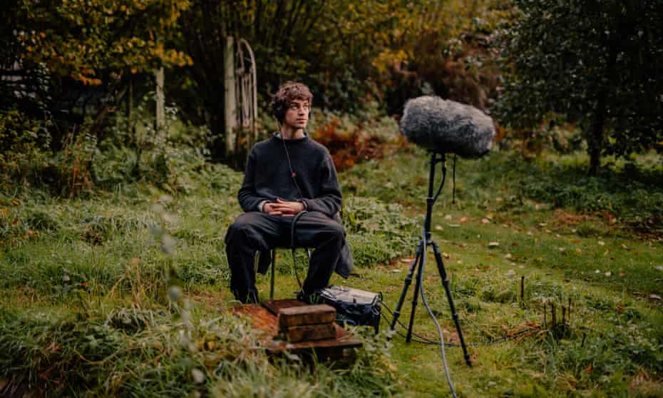 Musician Cosmo Sheldrake listens to dawn bird songs through his recording equipment, outside his home. Fordingbridge, Hampshire, UK. 23rd October 2020.