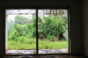 A broken window in the abandoned Sheraton hotel in the Cook Islands