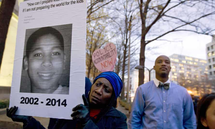 Tomiko Shine holds up a poster of Tamir Rice during a protest in Washington, 1 December 2014.
