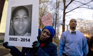 A woman holds up a poster of Tamir Rice during a protest in Washington DC in 2014.