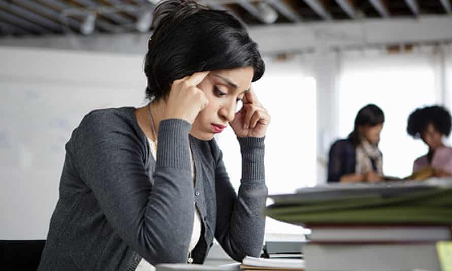 Stressed female office worker touching forehead