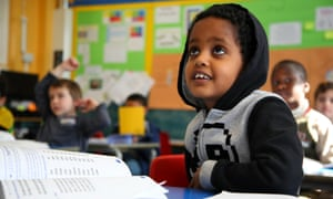 A child in a classroom looks up towards the teacher